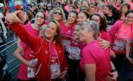 La campeona mundial y olímpica de natación Mireia Belmonte (c) posa para un selfi momentos antes de la salida de la decimocuarta edición de la Carrera de la Mujer, en la que las 16.000 participantes lucen en su camiseta rosa el número 016 contra la violencia machista.