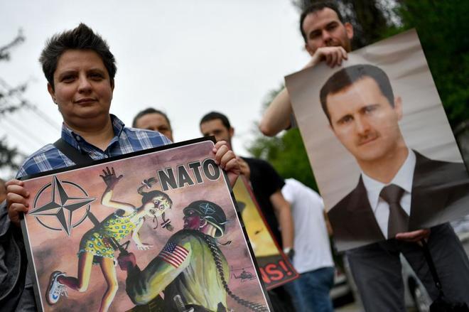 Ciudadanos serbios protestan contra el ataque en Siria con carteles del presidente Asad.
