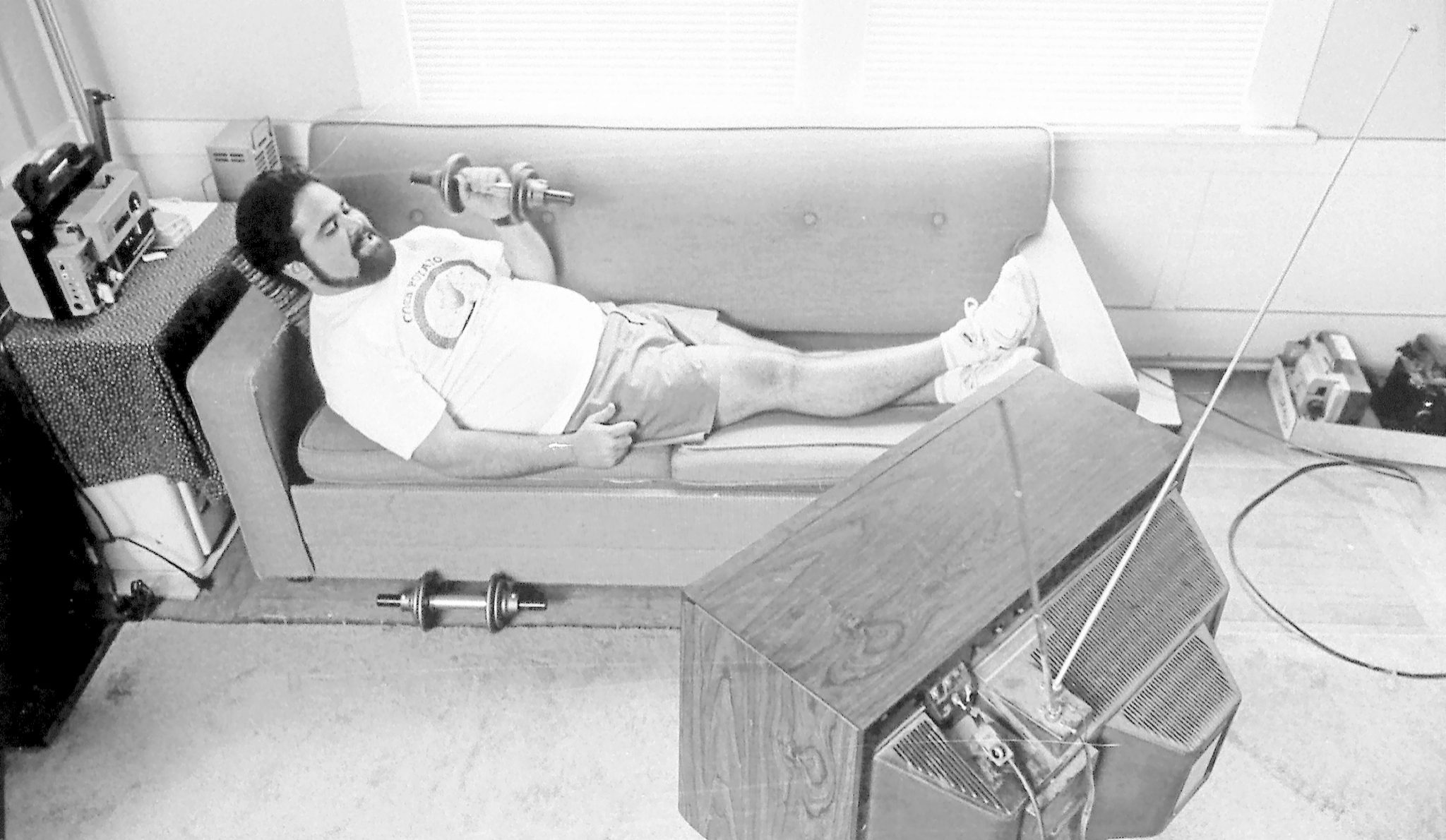 Un hombre, haciendo pesas en el sofá.