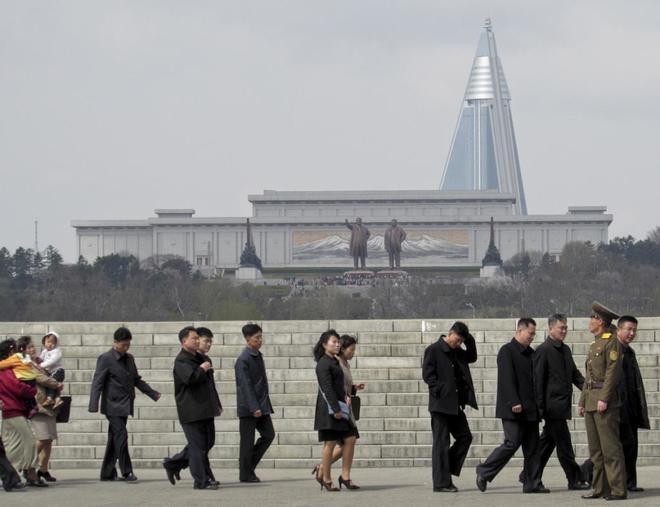 Norcoreanos hacen cola para acudir al festival floral de Pyongyang.