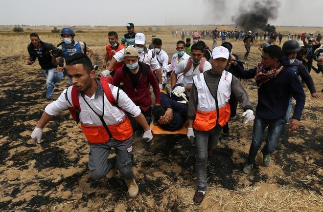 Un palestino herido es trasladado en camilla durante los choques con el ejército israelí en la frontera.