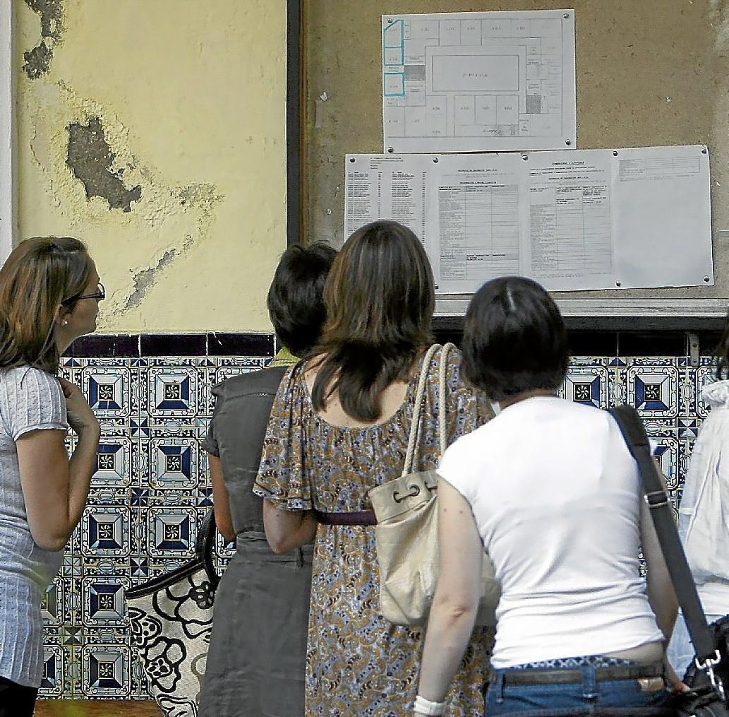 Un grupo de profesoras interinas observa los listados en las oposiciones.