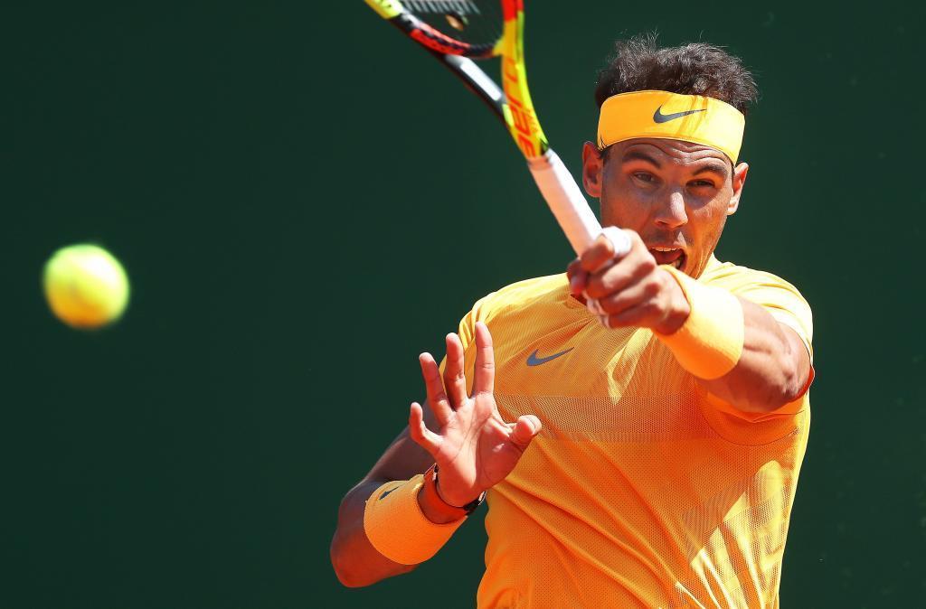 EPA7936. ROQUEBRUNE CAP MARTIN (FRANCIA), 20/04/2018.- El tenista español Rafa Nadal devuelve la bola al austriaco Dominic Thiem durante el partido de cuartos de final del Masters 1.000 de Montecarlo en Roquebrune Cap Martin en Francia hoy, 20 de abril de 2018. El español Rafael Nadal, número uno mundial, apenas se despeinó ante el austríaco Dominic Thiem, quinto favorito, al que arrolló con un contundente 6-0 y 6-2, accediendo a las semifinales del Masters 1.000 de Montecarlo, donde se medirá al búlgaro Grigor Dimitrov. EFE/ Sebastien Nogier