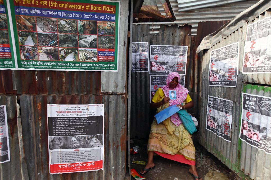 Una familiar de una de las víctimas del derrumbe del Rana Plaza sostiene una imagen de la víctima, durante una ceremonia de homenaje el día en que se cumple un lustro de la tragedia, en Daca.