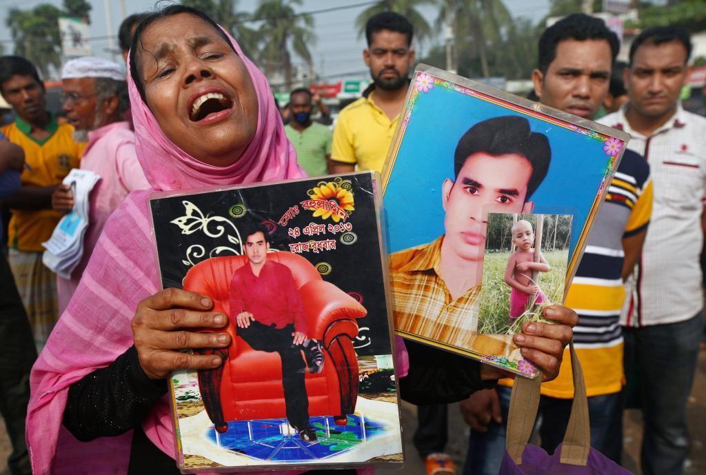 Una mujer llora con la foto de su familiar muerto en el derrumbe durante el homenaje a las víctimas, hoy en Daka.