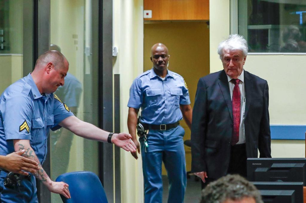 El ex líder serbobosnio Radovan Karadzic (dcha) a su llegada a la sala del tribunal del Mecanismo para los Tribunales Penales Internacionales (MICT).