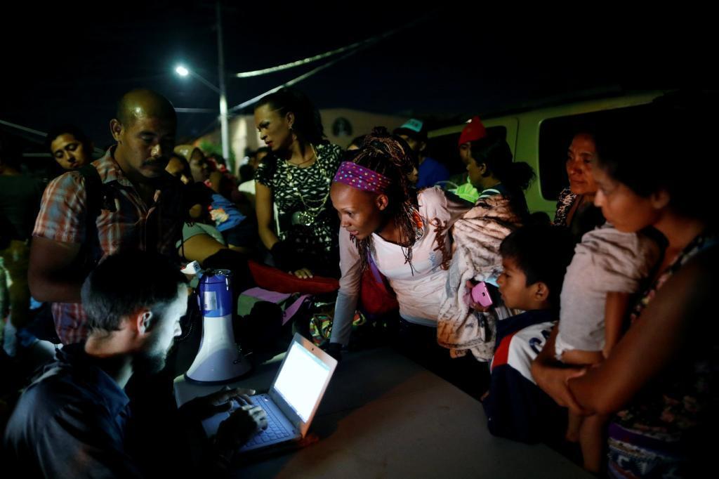 Migrantes se apuntan en una lista antes de emprender el viaje a la frontera, a Tijuana.
