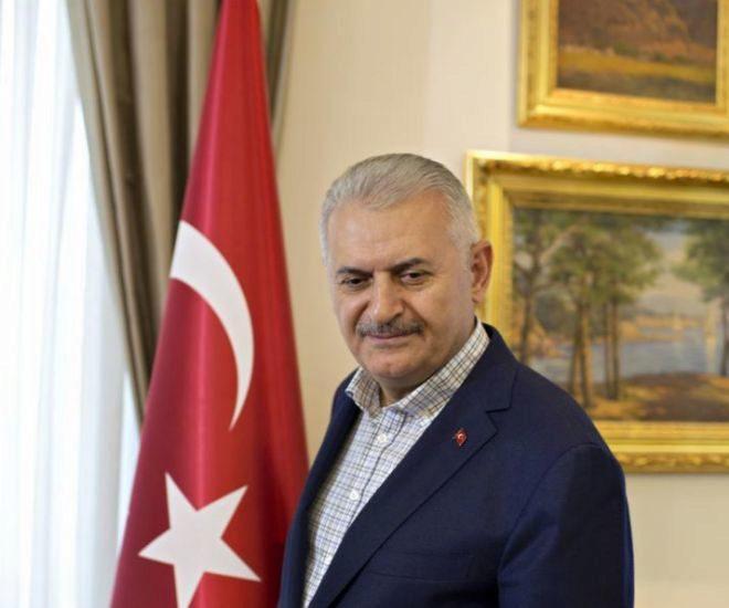 El primer ministro de Turquía, Binali Yildirim, junto a la bandera de su país.
