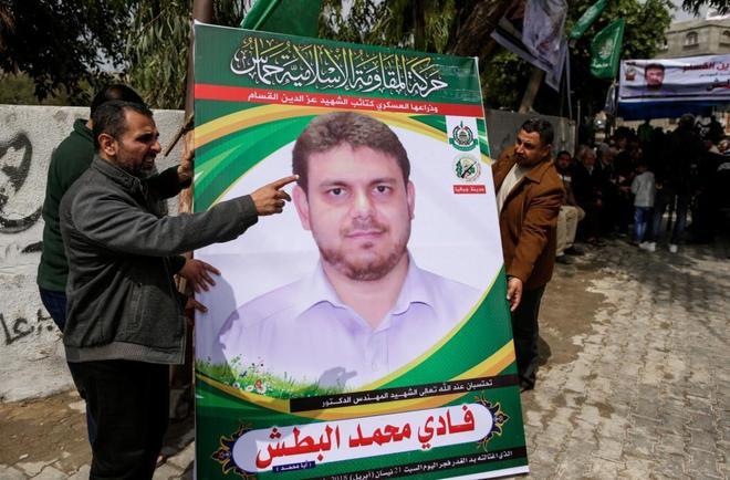 Varios hombres sostienen un cartel con la foto del ingeniero asesinado a las afueras de la casa de su familia en Gaza.