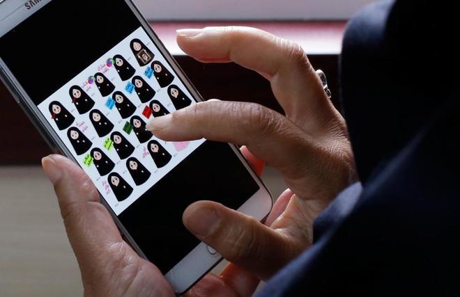 Una mujer iraní selecciona uno de los emoticonos con mensajes políticos de la app de mensajería para móviles Soroush.