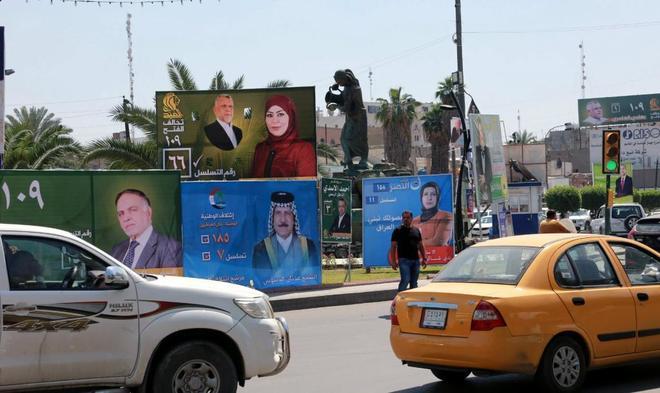Varios vehículos pasan delante de varios carteles electorales en la plaza Kahramana de Bagdad.