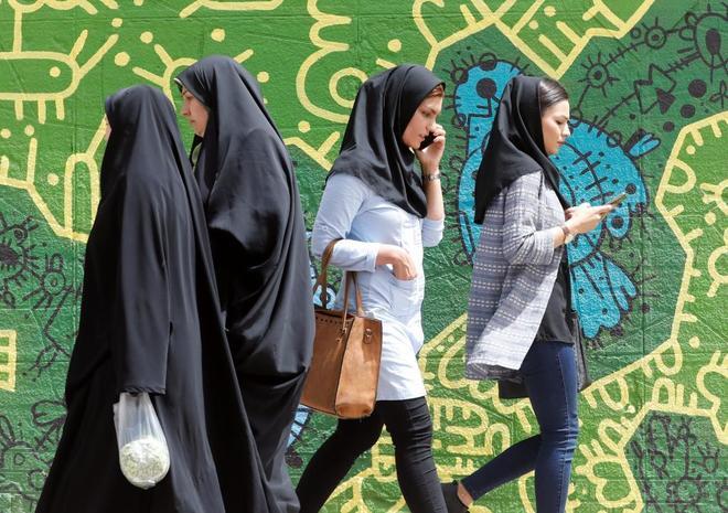 Mujeres iraníes consultando o hablando por su móvil en Teherán.