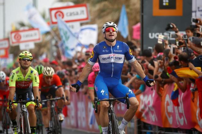 Elia Viviani celebra su victoria al sprint en la línea de meta.