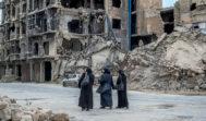 Tres mujeres caminan por una calle de Alepo, entre escombros y edificios derruidos.