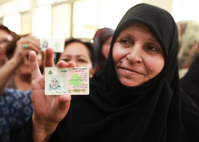 Una mujer libanesa muestra su carnet de identidad en la cola para votar en Beirut.