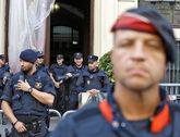 Un 'mosso' en primer plano, con agentes de la Policía Nacional...