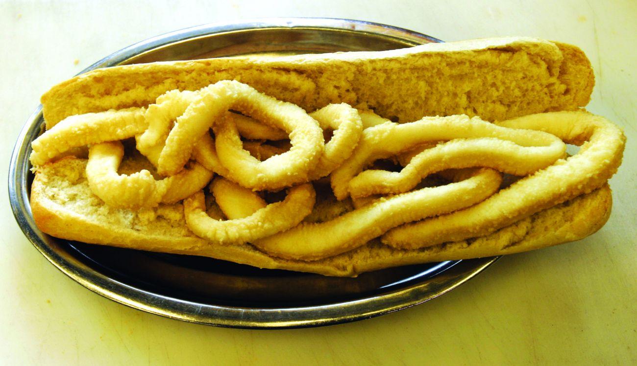 Anillos de calamar rebozados y fritos servidos en pan crujiente y con...