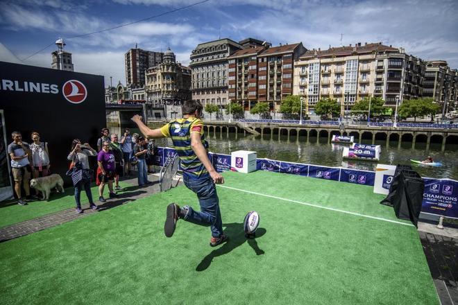 Un aficionado muestra su pericia para lanzar el balón de un lado a otro de la ría en la 'fan zone'.
