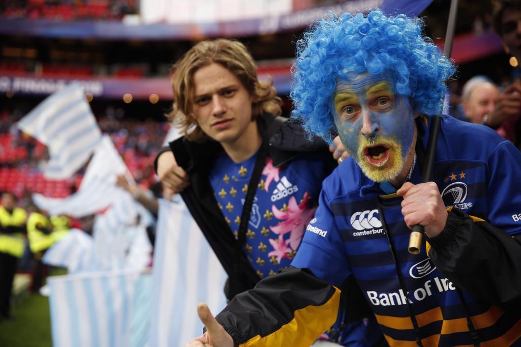 Dos aficionados de Leinster celebran la victoria entre banderas del equipo rival