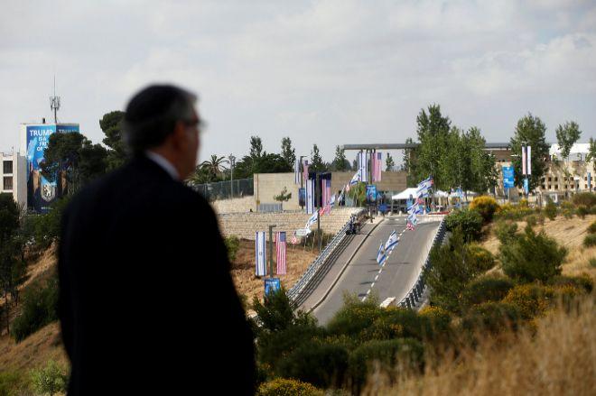 Una persona mira al camino, engalanado con las banderas israelíes e...