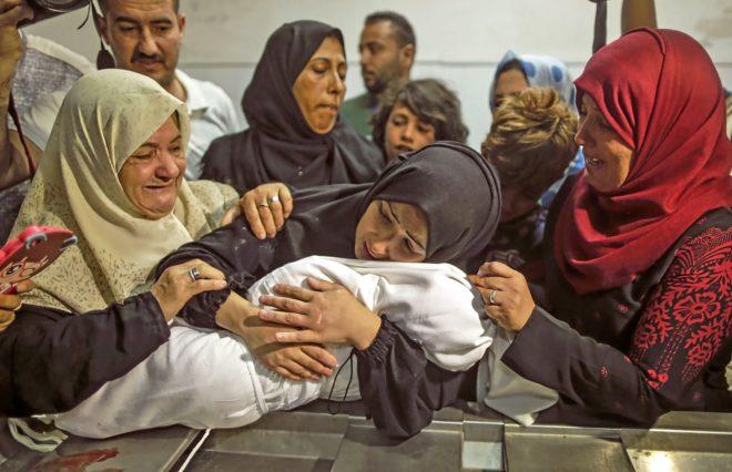 La madre de la bebé muerta supuestamente por gases lacrimógenos israelíes abraza el cuerpo de su hija.