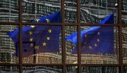 Dos banderas de la Unión Europea, reflejadas en el edificio del...