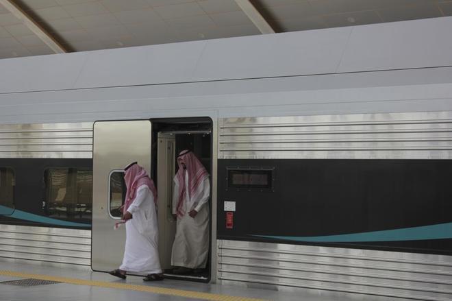 Dos hombres se apean de un tren convencional de la empresa española CAF, en la estación de ferrocarril de Riad.