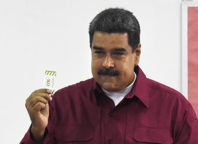 Nicolás Maduro muestra su carnet antes de votar en las presidenciales venezolanas.