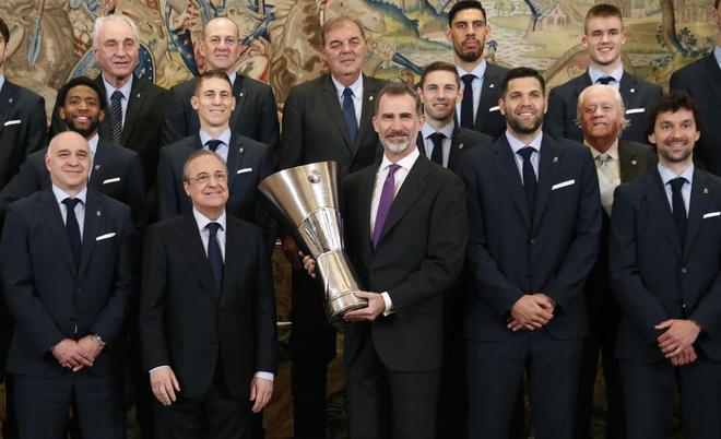 El rey Felipe VI posa con el trofeo junto a Florentino Pérez y los jugadores.