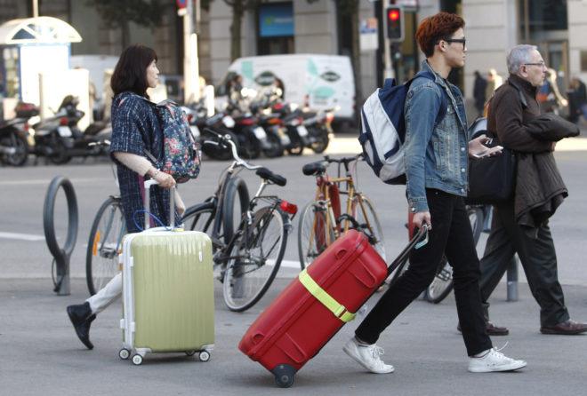 Dos turistas caminan por el centro de Barcelona.