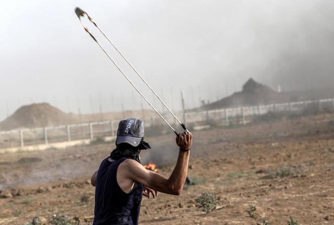 Un palestino lanza piedras cerca de franja de Gaza.