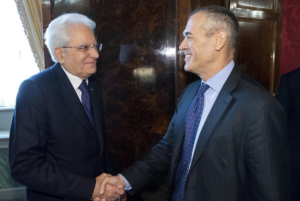Mattarella (izquierda) estrecha la mano de Cottarelli tras encargarle formar Gobierno.