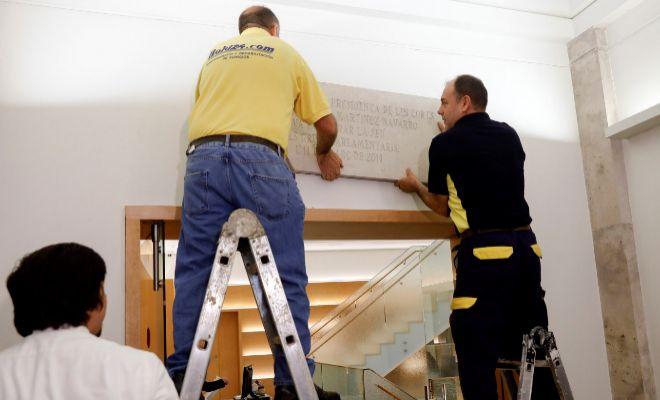 Los operarios retiran la placa oficial con el nombre de Milagrosa Martínez de las Cortes.