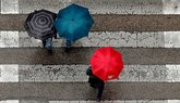 Varias pesonas cruzan un paso de cebra protegidas por paraguas en...