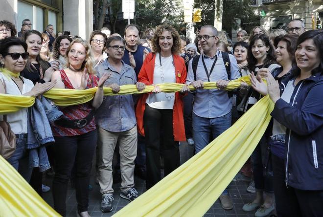 La nueva consellera de Justicia, Ester Capella (c), ha sido recibida, en su primer dia en la sede de su departamento, con un gran lazo amarillo y aplausos por parte de los trabajadores que la esperaban en la puerta.