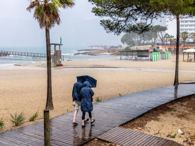 Varias personas se protegen de la lluvia mientras pasean por la playa de Camp de Mar, en Mallorca.