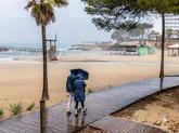 Varias personas se protegen de la lluvia mientras pasean por la playa...