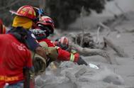 Bomberos retiran cenizas con palas durante la búsqueda de víctimas de la erupción.