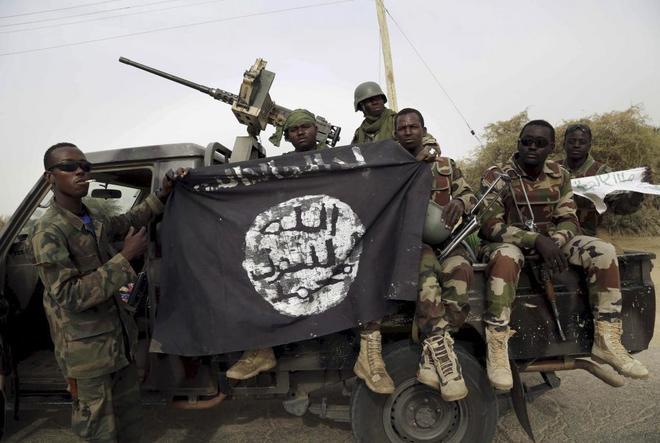 Soldados nigerianos exhiben una bandera capturada a Boko Haram en Damasak.