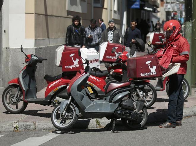 Un repartidor de Telepizza prepara un pedido para transportar en Madrid.