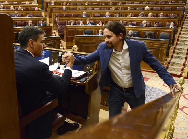 Pedro Sánchez y Pablo Iglesias se estrechan la mano durante el debate...