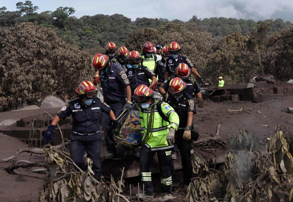 Un grupo de bomberos municipales extrae el cadáver de una víctima en...