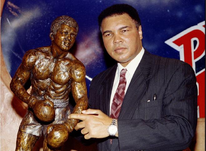 Muhammad Ali sostiene una estatua de sí mismo tras ingresar al Salón de la Fama de Boxeo.