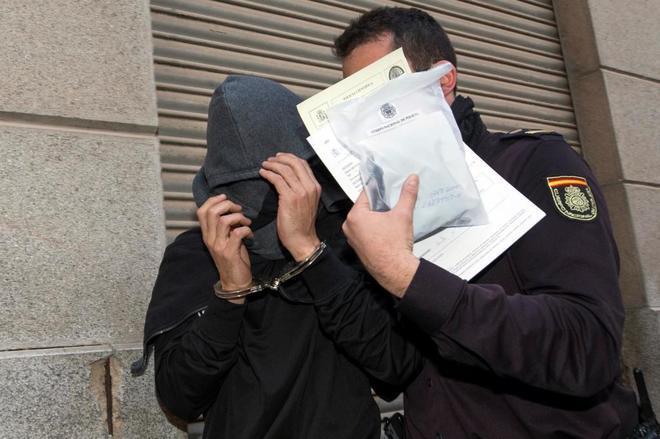 Un policía nacional traslada a uno de los jugadores detenidos en febrero, en la 'operación  Pizarro'