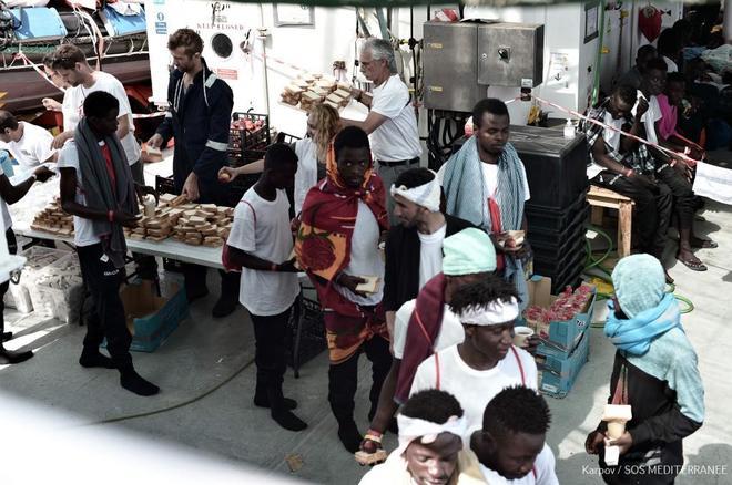 Inmigrantes del 'Aquarius' reciben provisiones a bordo del barco, según una imagen facilitada por la ONG SOS Mediterráneo.