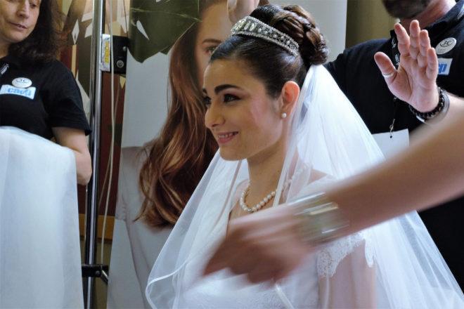 Un peluquero coloca el velo de la novia Rita Fonseca.