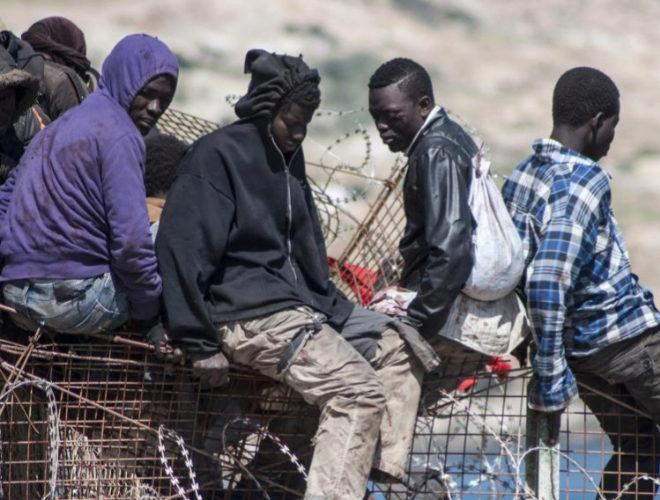 Inmigrantes africanos sentados en la altura de la valla de Melilla