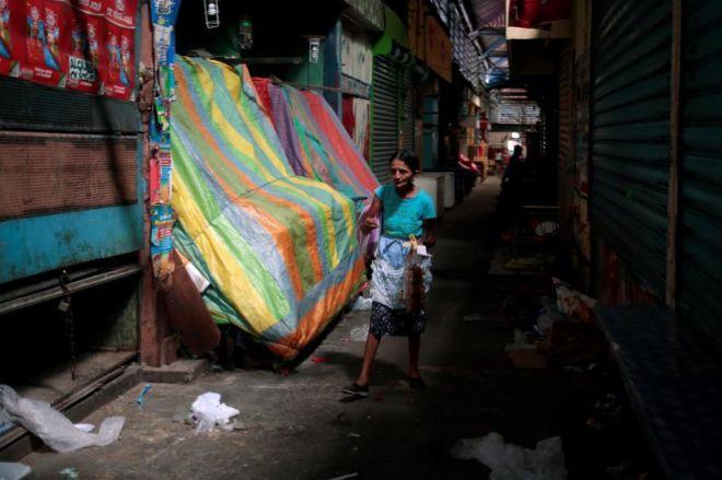 Una mujer camina por el mercado capitalino de Roberto Huembes que sumó al paro general del jueves.