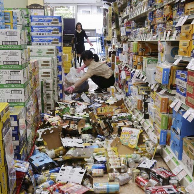 Empleados de una tienda recogen el género que ha caído como consecuencia del terremoto sufrido este lunes en Japón.
