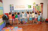 Un grupo de niños aprende la tabla periódica jugando en un colegio.